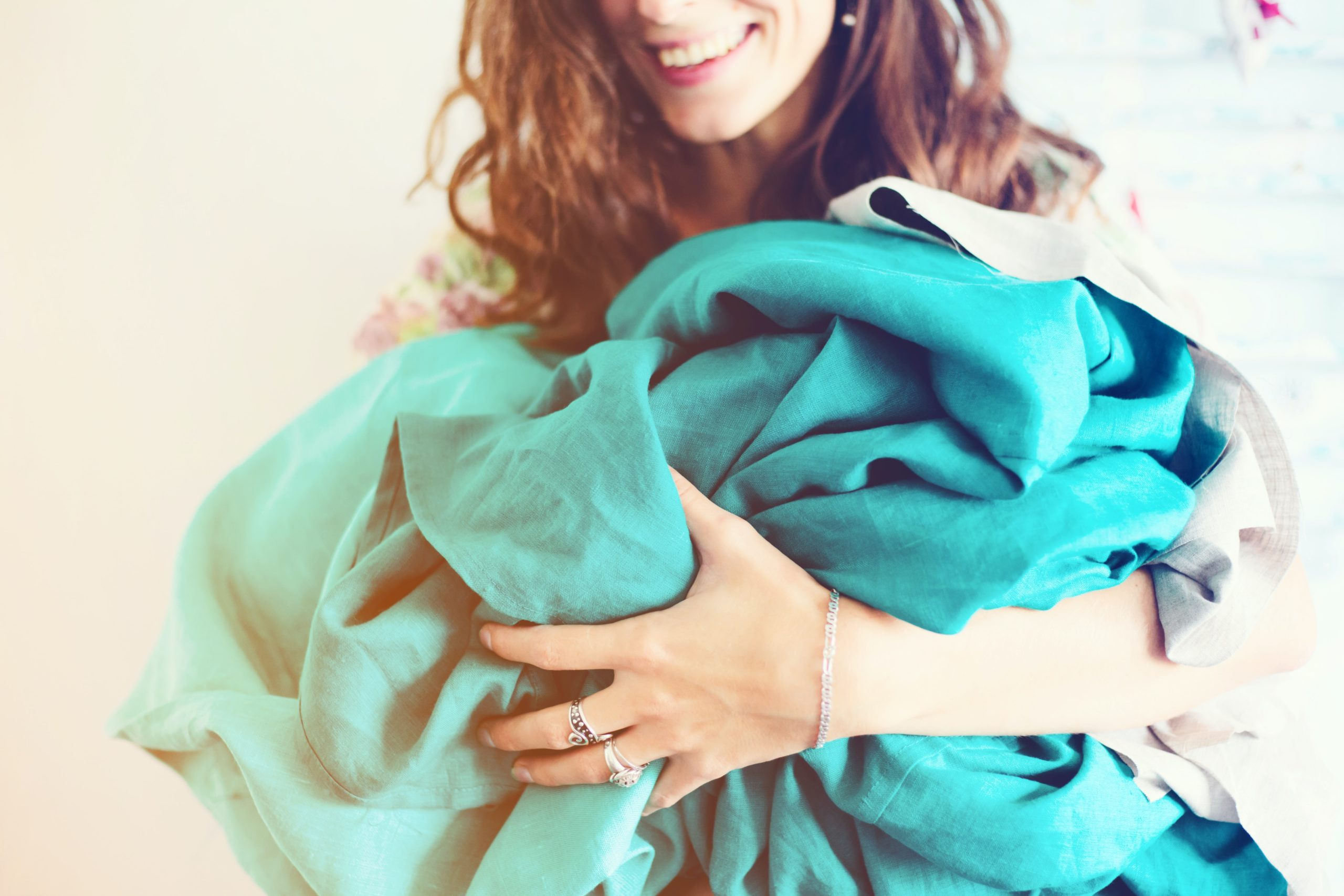 happy woman holding a pile of recycled clothes